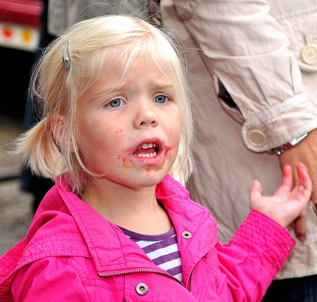 dutch girl: Made, Noord-Brabant, Netherlands - September 26, 2010 - Colorful fair in a small Dutch village, little blonde girl with red spots around her mouth grabs the hand of her mother (close-up)