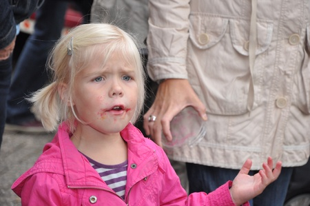 Made, Noord-Brabant, Netherlands - September 26, 2010 - Colorful fair in a small Dutch village, little blonde girl with red spots around her mouth grabs the hand of her mother Stock Photo - 8728669