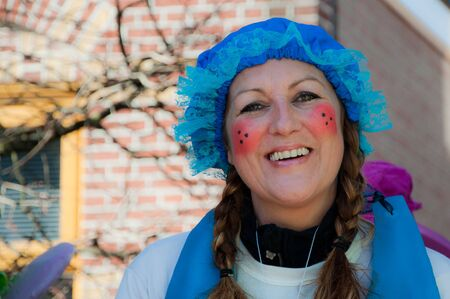 drimmelen: Made, North-Brabant, Netherlands – March 6, 2011 - Dutch carnival in the streets of a small village, portrait of a pretty woman with blue hat