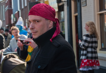 drimmelen: Made, North-Brabant, Netherlands – March 6, 2011 - Dutch carnival in the streets of a small village, man wih red scarf