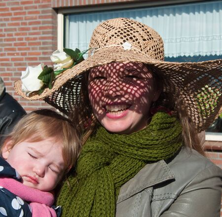 drimmelen: Made, North-Brabant, Netherlands – March 6, 2011 - Dutch carnival in the streets of a small village, portrait of young mother with sleeping child