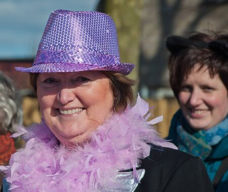 drimmelen: Made, North-Brabant, Netherlands – March 6, 2011 - Dutch carnival in the streets of a small village, middle aged woman with lilac hat and boa