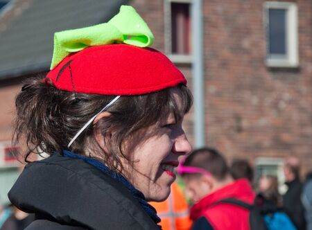 drimmelen: Made, North-Brabant, Netherlands – March 6, 2011 - Dutch carnival in the streets of a small village, smiling woman with red cap