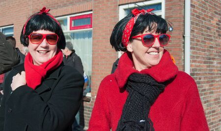 drimmelen: Made, North-Brabant, Netherlands – March 6, 2011 - Dutch carnival in the streets of a small village,  two women with blacks wigs, red ribbons and sunglasses Editorial