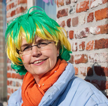 drimmelen: Made, North-Brabant, Netherlands – March 6, 2011 - Dutch carnival in the streets of a small village, middle aged woman with colorful wig