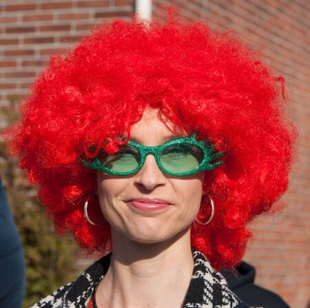 drimmelen: Made, North-Brabant, Netherlands – March 6, 2011 - Dutch carnival in the streets of a small village, younhg woman with a ornage wig and green glasses