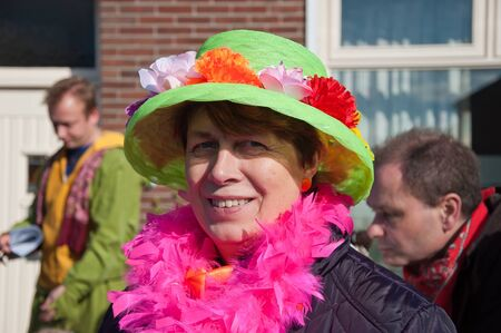 drimmelen: Made, North-Brabant, Netherlands – March 6, 2011 - Dutch carnival in the streets of a small village, smiling woman with green har and pink boa