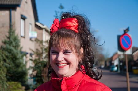 drimmelen: Made, North-Brabant, Netherlands – March 6, 2011 - Dutch carnival in the streets of a small village, portrait of smiling woman with a red ribbon in her hair