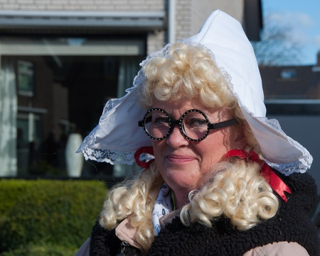 drimmelen: Made, North-Brabant, Netherlands – March 6, 2011 - Dutch carnival in the streets of a small village, woman with curly wig and starched cap