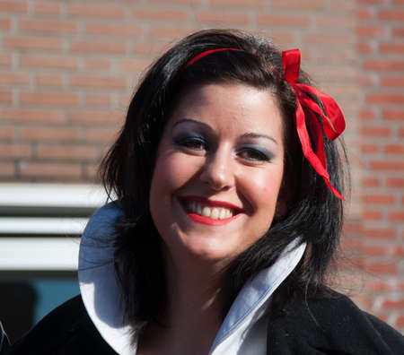 drimmelen: Made, North-Brabant, Netherlands – March 6, 2011 - Dutch carnival in the streets of a small village, pretty woman with black hair and red ribbon