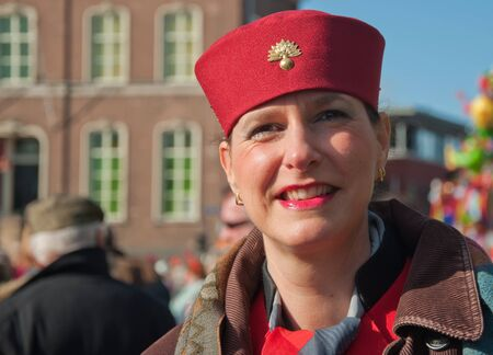 drimmelen: Made, North-Brabant, Netherlands – March 6, 2011 - Dutch carnival in the streets of a small village, smiling woman with a red hat Editorial