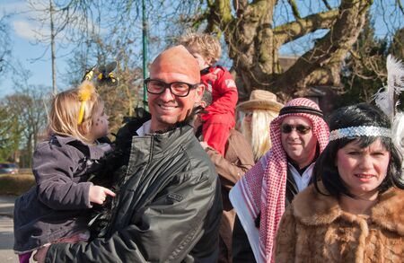 drimmelen: Made, North-Brabant, Netherlands – March 6, 2011 - Dutch carnival in the streets of a small village, costumed man with child Editorial