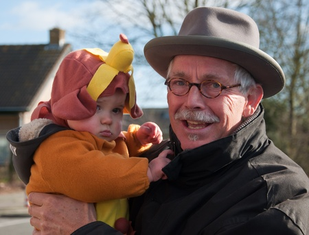 drimmelen: Made, North-Brabant, Netherlands – March 6, 2011 - Dutch carnival in the streets of a small village, man with costumed grandchild  Editorial
