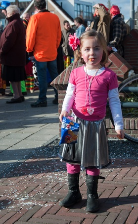drimmelen: Made, North-Brabant, Netherlands – March 6, 2011 - Dutch carnival in the streets of a small village, little girl with a bag of chips