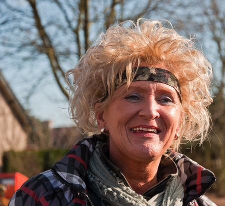 drimmelen: Made, North-Brabant, Netherlands – March 6, 2011 - Dutch carnival on the streets of a small village, woman with blonde wig