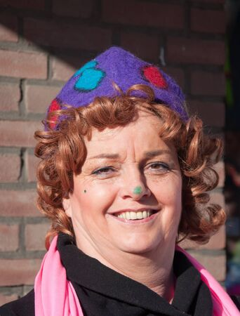 drimmelen: Made, North-Brabant, Netherlands – March 6, 2011 - Dutch carnival on the streets of a small village, smiling costumed woman