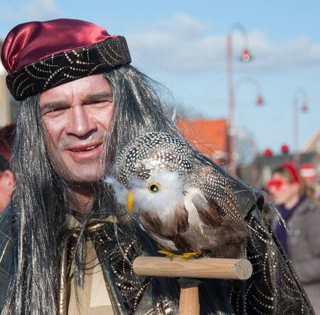 drimmelen: Made, North-Brabant, Netherlands – March 6, 2011 - Dutch carnival on the streets of a small village, man with bird
