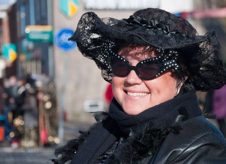 drimmelen: Made, North-Brabant, Netherlands – March 6, 2011 - Dutch carnival on the streets of a small village, woman with blach hat and sunglasses