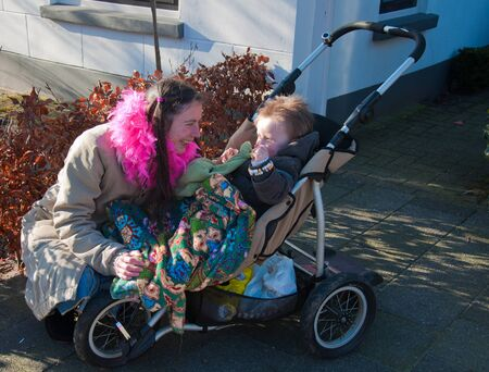 drimmelen: Made, North-Brabant, Netherlands – March 6, 2011 - Dutch carnival on the streets of a small village, mother with her child