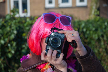 made in netherlands: Made, North-Brabant, Netherlands – March 6, 2011 - Dutch carnival on the streets of a small village, woman with pink wig is photographing the photographer