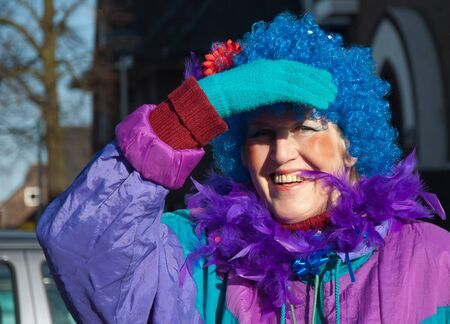 drimmelen: Made, North-Brabant, Netherlands – March 6, 2011 - Dutch carnival on the streets of a small village, woman with blue wig