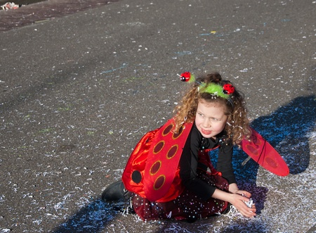 drimmelen: Made, North-Brabant, Netherlands – March 6, 2011 - Dutch carnival on the streets of a small village, little girl picks up confetti on the streets Editorial