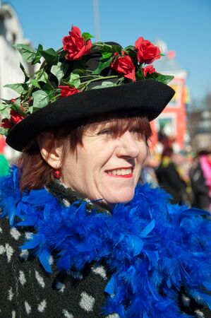 breda: Breda, North-Brabant, Netherlands – March 7, 2011 – Carnival Parade,  impression of the people, costumed woman with blue boa and hat
