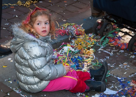 Breda, North-Brabant, Netherlands – March 7, 2011 – Carnival Parade,  impression of the people, little girl sitting on the street is playing with confetti