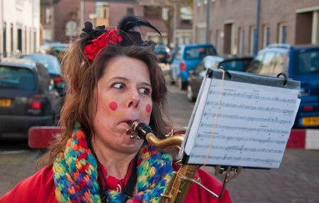 breda: Breda, North-Brabant, Netherlands – March 7, 2011 – Carnival Parade,  impression of the people, costumed woman is playing saxophone Editorial