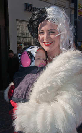 Breda, North-Brabant, Netherlands – March 7, 2011 – Carnival Parade,  impression of the people, happy young mother with baby