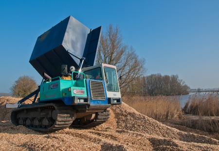 dumping: Caterpillar sidetipper is dumping woodchips Stock Photo