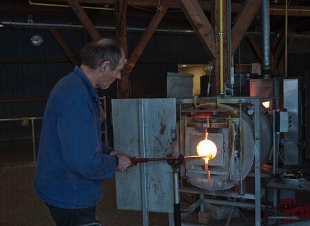 Leerdam, Netherlands -  December 10, 2010: Master glass blower is creating a vase  Stock Photo - 9204814