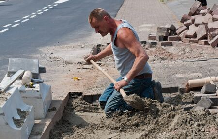 made in netherlands: Made, North-Brabant, Netherlands, May 5, 2011,  Bragging sand by a road worker Editorial