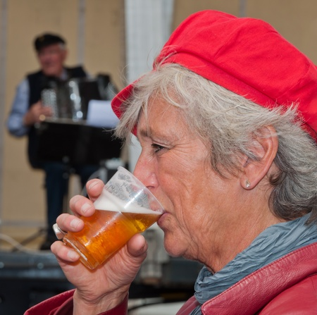 Drimmelen, North-Brabant, Netherlands, May 29, 2011,  portrait of a dutch woman with a red cap drinking beer