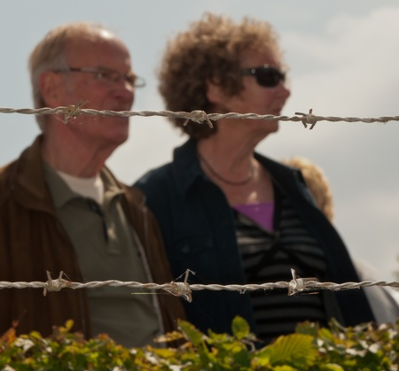 drimmelen: Drimmelen, North-Brabant, Netherlands, May 29, 2011,  A blurred duo portrait of a couple behind sharp barbed wire at the foreground
