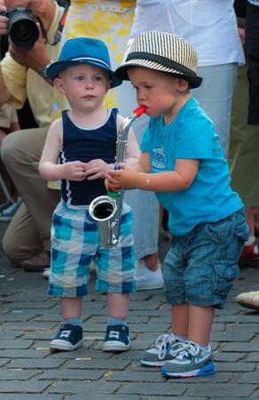 Breda, Nordbrabant, Niederlande, 4. Juni 2011, Jazzfestval 2011, imitieren Zwei Kleinkinder der Saxophonist auf der Bühne.