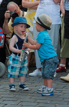 Breda, North-Brabant, Netherlands, June 4, 2011, Jazzfestval 2011,  Two toddlers imitate the saxophone player on stage.