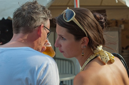 Breda, North-Brabant, Netherlands, June 4, 2011, Jazzfestval 2011,  Woman is whispering something in the ear of a man