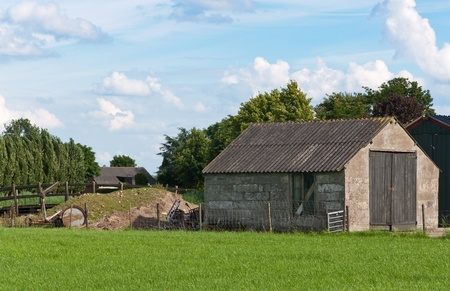 Dussen, North-Brabant, Netherlands, June 24, 2011, An old barn in a Dutch landscape with grass in the foreground Stock Photo - 9777504