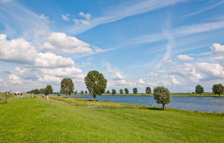 A typical Dutch landscape with grass, clouds and a river photo