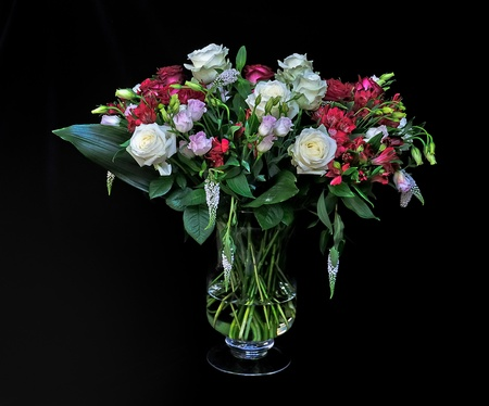 A bouquet of mixed flowers against a black background Stockfoto