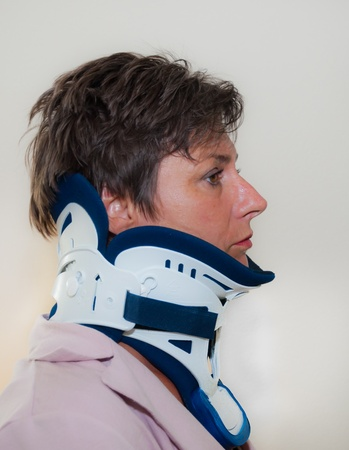 Breda, North-Brabant, Netherlands, July 17, 2011, Profile of woman with a hard neck collar against a light background