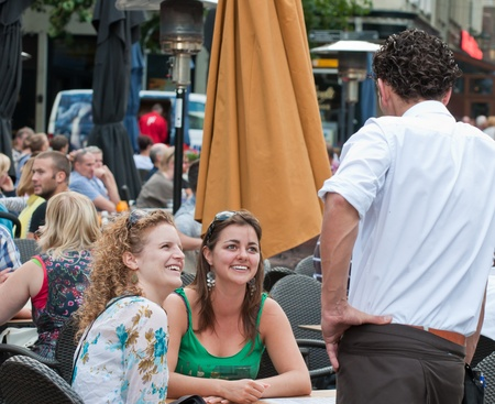 Breda, North-Brabant, Netherlands, August 15,  2011, Two young women sitting at a terrace at6 the Grote Markt and flirting with the waiter