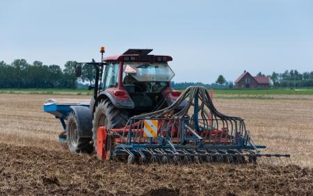 Bauernhof Traktor und Rasensämaschine auf der Rückseite, die Arbeiten in einem niederländischen Feld