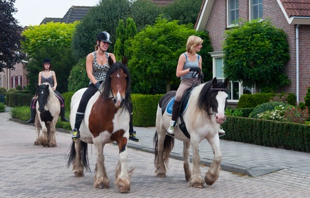 Made, North-Brabant, Netherlands, August 21, 2011, Three girls riding om Belgian horses in a street of the Dutch village of Made