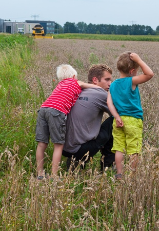 Made, North-Brabant, Netherlands, August 21, 2011, Father and his two sons watching harvesting by the yellow combine in the background