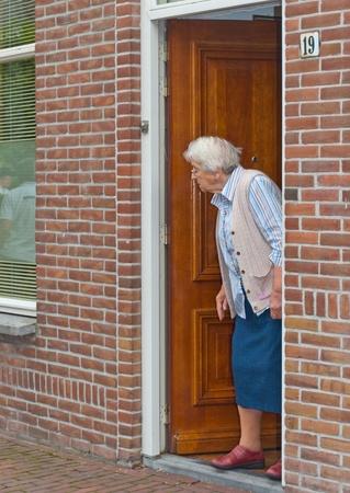 Terheijden, del Brabante Settentrionale, Paesi Bassi, 28 agosto 2011, vecchia donna guarda fuori porta het Archivio Fotografico - 10434279