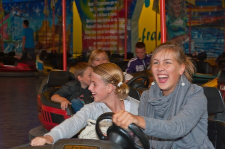 den: Fun fair in the small Dutch village of Den Hout, North Brabant. Excited girls in a bumper car at a fun fair in a village in the Netherlands on September 17, 2011