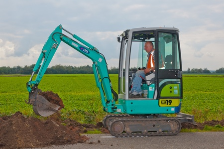 Ground engineering works in the Netherlands. Mini excavator is moving soil in the village of Wouw, North-Brabant, Netherlands on September 15, 2011. Stock Photo - 10592099