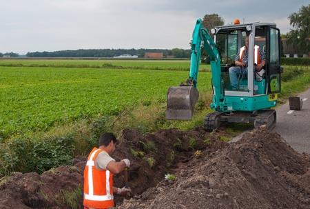 Geotechnik arbeitet in den Niederlanden. Der Mensch und Minibagger einen Graben, um Kabel in dem Dorf Wouw, Nord-Brabant, Niederlande lag am 15. September 2011.